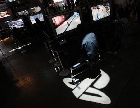 A man plays Sony's PlayStation 3 game console as logo of Sony's PlayStation displayed at the Tokyo Game Show in Chiba, east of Tokyo September 24, 2009. REUTERS/Toru Hanai