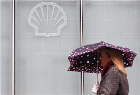 A woman shelters under an umbrella as she walks past the Shell Centre in London February 4, 2010. REUTERS/Luke Macgregor