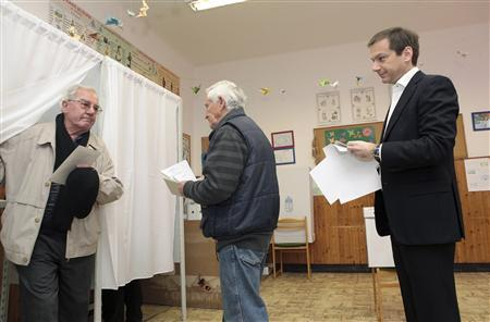 Hungarian Prime Minister Gordon Bajnai (R) waits to vote at a polling station during parliamentary elections in Budapest April 11, 2010. REUTERS/Prime Minister Press Office/Handout