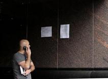 <p>Foto de archivo de una persona hablando por teléfono móvil a la salida de un banco Stanford en Ciudad de México, feb 20 2009. México continuaba el lunes el proceso de registro obligatorio de los teléfonos celulares luego de que venciera el plazo que tenían los usuarios para hacerlo, mientras las telefónicas aseguraban que poco a poco desconectarán millones de líneas no registradas. REUTERS/Henry Romero(MEXICO)</p>