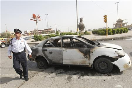 A traffic policeman walks past a damaged vehicle at the site of a bomb attack in Baghdad, April 14, 2010. REUTERS/Mohammed Ameen