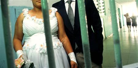 A woman and her husband pose behind bars at the Carandiru Prison in Sao Paulo June 14, shortly after Brazil's first-ever mass prison wedding. REUTERS/Stringer