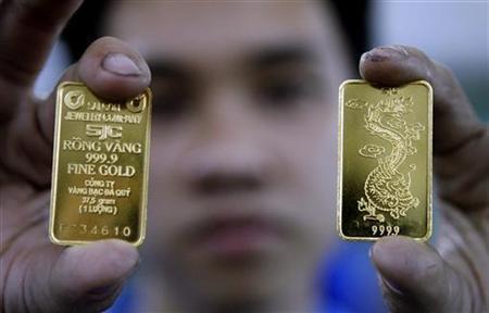 A man displays gold bars at SJC gold factory in Ho Chi Minh city January 22, 2010. REUTERS/Kham