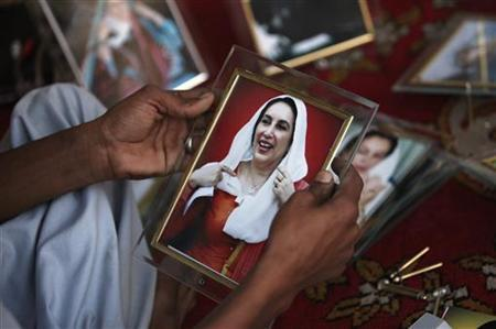 A man holds a portrait of the late Prime Minister Benazir Bhutto while displaying her images at a makeshift memorial in Liaquat Bagh in Rawalpindi March 31, 2010. REUTERS/Faisal Mahmood