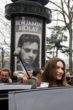 <p>A primeira-dama francesa, Carla Bruni-Sarkozy, chega à estação de votação para as eleições regionais. O cantor francês Benjamin Biolay (pôster ao fundo) venceu um processo judicial contra a emissora de TV France 24 depois que o canal comentou sobre um suposto caso com Bruni. 14/03/2010 REUTERS/Eric Feferberg/Arquivo</p>