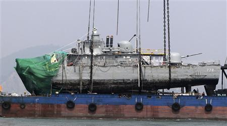 Salvage team members and rescue workers put a part of a sunken naval vessel on a barge after they lifted it with a giant crane, off Baengnyeongdo island near the maritime border with North Korea, northwest of Seoul April 15, 2010. REUTERS/Lim Hun-jung/Yonhap