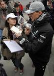 <p>Michael Schumacher, da Mercedes, dando autógrafos a fãs em Xangai. Mesmo longe da pole, Schumacher é idolatrado pelos chineses. REUTERS/David Gray</p>