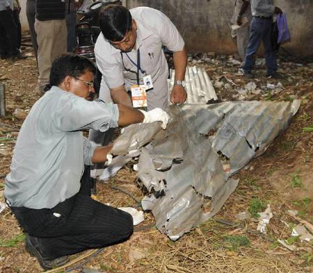 Forensic experts inspect the site of a bomb blast outside a cricket stadium in Bangalore April 17, 2010. At least 10 people were wounded when two bombs exploded on Saturday outside a packed cricket stadium in Bangalore, stirring fears about more militant attacks, police said. REUTERS/Stringer