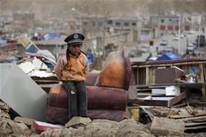 <p>Девочка сидит на развалинах дома, разрушенного землетрясением в округе Юйшу, в провинции Цинхай 18 апреля 2010 года. Число жертв землетрясения в горной провинции Цинхай на юго-западе Китая выросло до 1.944 человек, сообщили государственные СМИ в понедельник. REUTERS/Stringer</p>