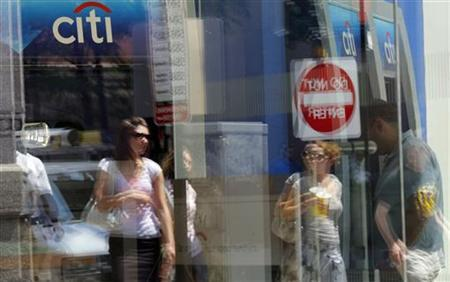 Pedestrians are reflected in the window of a Citibank branch in Boston, July 17, 2009. REUTERS/Brian Snyder