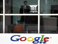 <p>Una guardia di sicurezza guarda dei giornalisti dall'interno della sede di Google China a Pechino REUTERS/David Gray</p>