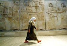 <p>An Iraqi woman walks in front of Assyrian mural sculptures July 3, 2003 as the Baghdad museum briefly re-opens to display ancient Nimrud treasures. REUTERS/Radu Sigheti</p>