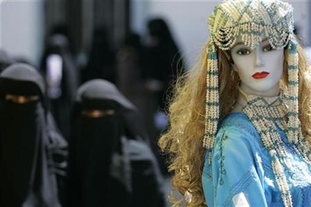 Veiled women walk past a mannequin at a shopping bazaar in Sanaa March 1, 2009. REUTERS/Khaled Abdullah