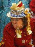 <p>Женщина в декорированной сыром шляпе танцует на фестивале на рынке Виктуалиенмаркт в Мюнхене 24 февраля 2009 года. Австралийский суд приговорил женщину к 25 годам тюремного заключения за убийство молодого человека, бросавшего в ее автомобиль сырными шариками. REUTERS/Alexandra Beier</p>
