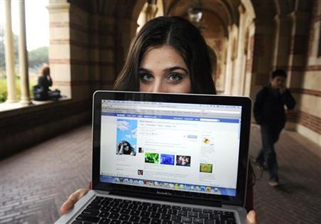 A woman displays her page on the social networking site Facebook, while attending school in Los Angeles January 26, 2010. REUTERS/Phil McCarten