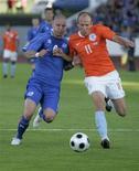 <p>Игрок сборной Нидерландов Арьен Роббен борется за мяч с исландцем Гретаром Стейнссоном во время отборочного матча ЧМ-2010 в Рейкьявике 6 июня 2009 года. Тренер сборной Японии по футболу Такеси Окада озадачен потрясающей формой, в которой находится голландец Арьен Роббен, и считает, что матч против Нидерландов будет самым серьезным испытанием для его команды на групповом этапе чемпионата мира в ЮАР. REUTERS/Ingolfur Juliusson</p>