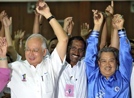 Flanked by Malaysia's Prime Minister Najib Razak (L) and his deputy Muhyiddin Yassin, P. Kamalanathan of the ruling National Front coalition celebrates after winning the Hulu Selangor parliamentary by-election in Hulu Selangor outside Kuala Lumpur April 25, 2010. REUTERS/Samsul Said