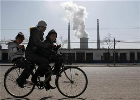 Two young children ride a bicycle with their mother past abandoned buildings in front of a chimney billowing smoke from a nearby coal-burning power station in Beijing March 10, 2010. REUTERS/David Gray