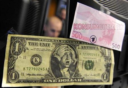 A share trader is pictured behind a mock one dollar bill and a mock 500 Euro note symbolizing a consumer credit note, at the German stock exchange in Frankfurt, December 18, 2008. REUTERS/Kai Pfaffenbach