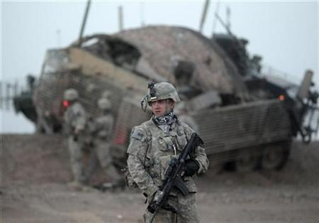 A soldier from the U.S. Army's 3rd Platoon, Centurion Company, 2-1 Infantry Battalion, 5/2 Stryker Brigade Combat Team stands near a disabled armoured vehicle during an operation in Maiwand District, Kandahar Province, April 20, 2010. REUTERS/Tim Wimborne