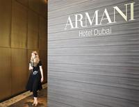 <p>A woman passes by a logo at the world's first Armani Hotel at Burj Khalifa in Dubai, April 27, 2010. REUTERS/Mosab Omar</p>
