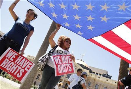 People hold the U.S. flag as they protest against Senate Bill 1070 outside the Arizona State Capitol in Phoenix, Arizona April 25, 2010. REUTERS/Joshua Lott