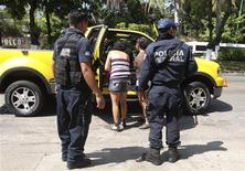 <p>Federal police stand guard as a vehicle undergoes a check at the Mexican beach resort of Acapulco April 25, 2010. REUTERS/Jesus Trigo</p>