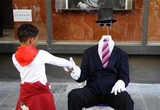 <p>A boy shakes hands with a street performer during the San Fermin festival in Pamplona July 7, 2008. REUTERS/Eloy Alonso</p>