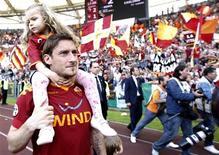 <p>Totti carrega sua filha ao fim da partida em Roma. Francesco Totti conseguiu reduzir os problemas do Roma ao marcar dois gols no final do jogo que garantiram a vitória do time da capital italiana por 2 x 1 sobre o Cagliari.06/05/2010.REUTERS/Alessandro Bianchi</p>