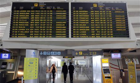 People walk underneath an information board showing cancelled flights at Bilbao Airport May 8, 2010. REUTERS/Vincent West