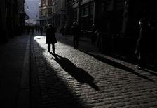 <p>City worker casts shadows in Leadenhall Market in the financial district of the City of London January 21, 2010. REUTERS/Luke MacGregor</p>