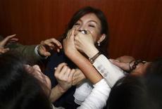 <p>Opposition Democratic Progressive Party (DPP) legislators cover the mouth of Nationalist (KMT) legislator Chao Li-yun during a parliament session inside the Legislative Yuan in Taipei April 21, 2010. REUTERS/Stringer</p>