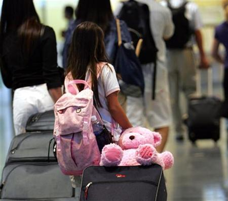 A girl drags her luggage with a teddy bear at the New Tokyo International Airport in Narita, east of Tokyo August 11, 2006. REUTERS/Toru Hanai