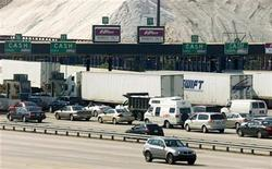 <p>A lone vehicle heading northbound (foreground) drives by as southbound traffic is at a crawl at the toll plaza to the entrance of the Fort McHenry Tunnel in Baltimore, Maryland October 18, 2005. REUTERS/Joe Giza</p>