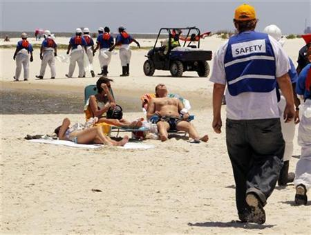 Clean-up crews comb the beach for tar balls washed on shore on Dauphin Island, Alabama May 10, 2010. REUTERS/Brian Snyder