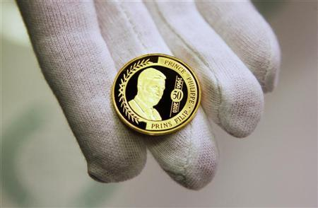 A worker displays a newly minted 100 euro gold special edition coin with the portrait of Belgium's Crown Prince Philippe at Belgium's Royal Mint in Brussels April 1, 2010. REUTERS/Francois Lenoir