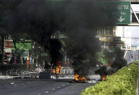 Smoke rises from burning tyres on a deserted road at the entrance of the business district during a rally by anti-government ''red shirt'' protesters in Bangkok May 15, 2010. REUTERS/Stringer