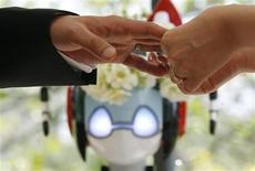 "<p>Satoko Inoue (R) puts on a wedding ring for Tomohiro Shibata in front of a humanoid robot named ""I-Fairy"" during their wedding ceremony in Tokyo May 16, 2010. ""The couple decided to use the robot, which conducted the ceremony with its audio functions, from Inoue's company to perform the witness' duties as they first met due to common work interest related to robots. REUTERS/Yuriko Nakao</p>"