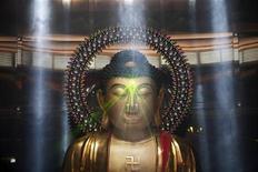 <p>La statua di Buddha che irradia fasci di luce durante una cerimonia funebre al Nirvana Memorial Garden. REUTERS/Edgar Su (SINGAPORE - Tags: RELIGION SCI TECH SOCIETY)</p>