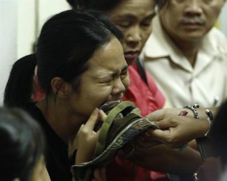 Khattiya Sawasdipol cries and holds up a cap of her father, renegade Thai major-general Khattiya Sawasdipol, at a hospital in Bangkok May 17, 2010. REUTERS/Sukree Sukplang