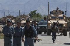 """<p>Афганские полицейские и конвой США недалеко от места атаки одной из крупнейших баз НАТО, Баграм 19 мая 2010 года. Боевики движения """"Талибан"""" рано утром атаковали одну из крупнейших баз НАТО в Афганистане, в результате чего было убито как минимум семь нападавших, а пять солдат коалиции получили ранения. REUTERS/Ahmad Masood</p>"""