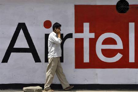 A man talks on a mobile phone in front of a Bharti Airtel advertisement in Jammu April 28, 2010.  REUTERS/Mukesh Gupta/Files