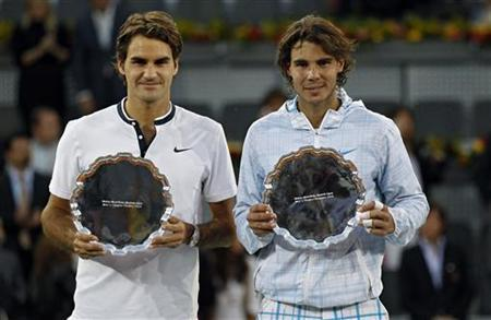 Rafael Nadal of Spain (R) and Roger Federer of Switzerland pose with their trophies at the end of their Madrid Open final tennis match May16, 2010. REUTERS/Juan Medina