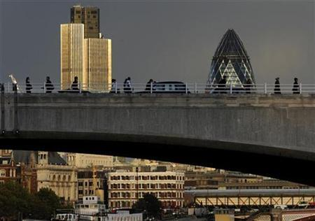 The skyline of the financial district of the City of London is seen behind workers crossing Waterloo Bridge during the evening rush-hour in central London October 16, 2008. REUTERS/Toby Melville