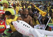<p>Fãs do futebol cantam durante reabertura do estádio Soccer City em Johanesburgo. A África do Sul reabriu as portas do estádio com uma grande festa neste sábado, marcando a disponibilização do último dos 10 estádios da Copa do Mundo antes do torneio. 22/05/2010 REUTERS/Siphiwe Sibeko</p>