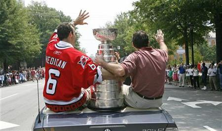 Carolina Hurricanes head coach Peter Laviolette (R) and Bret Hedican (L) hold onto the Stanley Cup as they wave to fans during a parade held in honor of the team's NHL Championship series win over the Edmonton Oilers in downtown Raleigh, North Carolina, June 21, 2006. REUTERS/Ellen Ozier