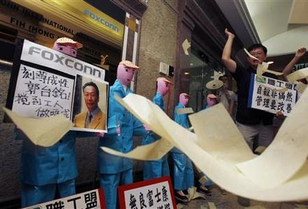 Protesters from several workers' rights groups throw paper money in front of paper figures, depicting workers who recently died in apparent suicides, during a traditional Chinese mourning ceremony outside a Foxconn office in Hong Kong May 25, 2010. An employee of the tech firm Foxconn died early on Tuesday after falling from a building in southern city of Shenzhen, state media reported, the ninth such death at the firm's manufacturing hub this year. The placard shows a portrait of Foxconn's founder, Taiwanese tycoon Terry Gou, and the Chinese characters read, ''Cruelty Gou Tai-ming''. REUTERS/Bobby Yip