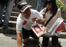 <p>O pai Ma Zishan e a irmã Ma Liqun lamentam a morte de Ma Xiangqian em frente à fábrica da Foxconn em Longhua, província chinesa de Guangdong. Eles vestiam branco, a cor tradicional do luto na China. 26/05/2010 REUTERS/Stringer</p>