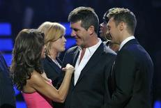 <p>Former American Idol judge Paula Abdul (L), judge Simon Cowell and host Ryan Seacrest are seen onstage after performing a tribute to Cowell at the American Idol Grand Finale 2010 in Los Angeles, May 26, 2010. REUTERS/Vince Bucci/Fox/PictureGroup/Handout</p>