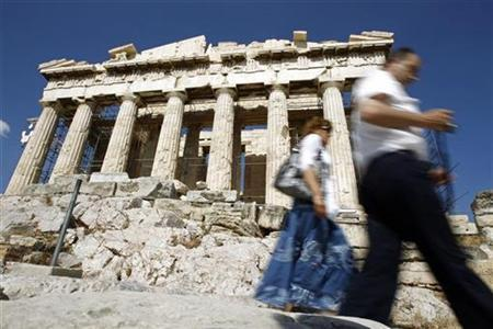 Tourists walk past the Parthenon on Acropolis hill in Athens May 18, 2010. REUTERS/Pascal Rossignol